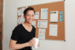 Young asian man standing indoors drinking tea. Stock Photos