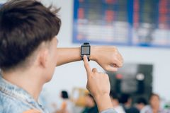 Young asian man standing near airline schedule and touching on h. Is watch Royalty Free Stock Photography