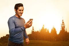 Young asian man standing in training clothes using his phone. Against sunset background Royalty Free Stock Photo