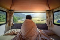 Young Asian man staying in the blanket in camper van. Young Asian man staying in the blanket looking at mountain scenery through the window in camper van in the royalty free stock image