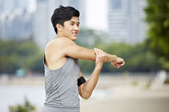 Young asian man stretching arms stock photography