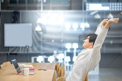 Young Asian man stretching out his arm in workspace. Young Asian man stretching out his arm during working with laptop computer in workspace. High school or Stock Photography