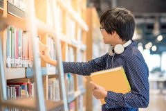 Young Asian man student choosing book in library. Education research and self learning in university life concepts Stock Photos