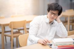 Free Young Asian Man Student Feeling Bored While Working In Library Royalty Free Stock Photo - 103894555
