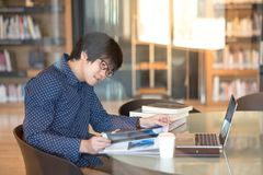 Young Asian man university student reading book in library. Young Asian man student reading book and magazine in public library, education research and self Royalty Free Stock Image