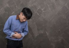 Young asian man suffer from severe stomachache. Background Stock Photo