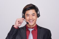 Young asian man in suit wearing a headset Royalty Free Stock Image