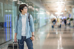Young Asian man with suitcase luggage in airport terminal Stock Images
