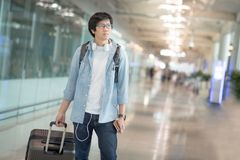 Young Asian man with suitcase luggage in airport terminal Royalty Free Stock Photos