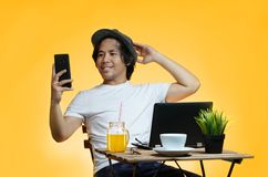 Young Asian Man Takes A Selfie While Working on Summer Vacation. Against Yellow Background Stock Image