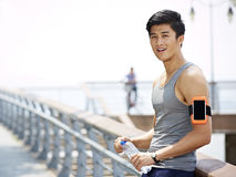 Young asian man taking a break during outdoor exercise stock images