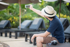 Young Asian man taking selfie shot on smartphone Stock Image