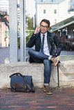 Young asian man talking on cellphone. Young asian business man talking on mobile phone sitting outside on city street royalty free stock photo