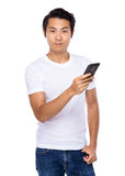 Young asian man texting message at his mobile phone Royalty Free Stock Photography