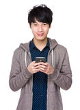 Young asian man texting message at his mobile phone Stock Image