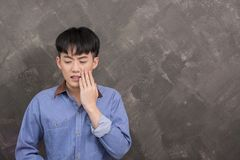Young asian man with a toothache tooth pain on the grunge backgr. Ound stock photography
