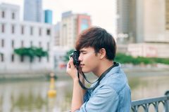 Young asian man tourist taking photos outdoor in the city.  Stock Photography