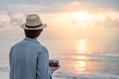 Young Asian man traveler looking sunset at tropical beach Royalty Free Stock Images