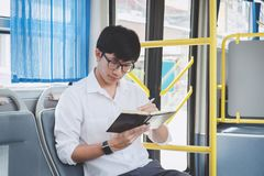 Young Asian man traveler sitting on a bus and reading book or practice homework exam while smile of happy day, transport, tourism royalty free stock image