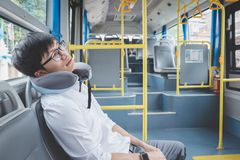 Young Asian man traveler sitting on a bus and sleeping with pillow, transport, tourism and road trip concept stock photos