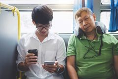 Young Asian man traveler sitting on a bus using smartphone for listening music and mature men sleeping with pillow, transport, royalty free stock photography