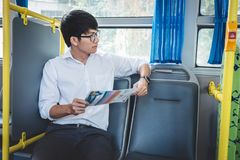 Young asian man traveler sitting on a bus while watching map to trip, transport, tourism and road trip concept stock photography