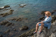 Young asian man traveler sitting on the rock cliff Royalty Free Stock Photos