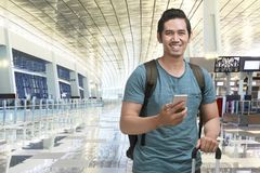 Young asian man traveling with suitcase and mobile phone. In airport terminal Royalty Free Stock Images