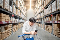 Young Asian man with trolley cart checking the shopping list in. Young Asian man standing with trolley cart checking the shopping list on his smartphone Royalty Free Stock Images