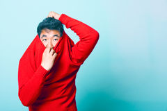 Young Asian Man trying to take of Red Sweater Royalty Free Stock Image