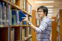Young Asian man university student choosing book in library. Education research and self learning in university life concepts Royalty Free Stock Photography