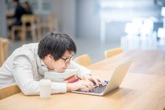 Young Asian man university student doing homework Royalty Free Stock Photos