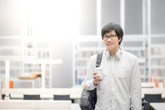 Young Asian man university student in library. Young Asian man university student with eyeglasses and headphones holding coffee cup in library, lifestyle in Stock Photos