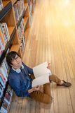 Asian man university student reading book in library. Young Asian man university student with glasses and headphones reading book sitting by bookshelf in public Stock Images