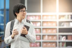 Young Asian man university student in library. Young Asian man university student holding laptop computer, notebook and coffee cup, happy lifestyle in college Stock Photo