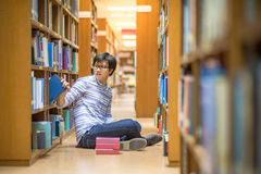 Young Asian man university student in library. Young Asian man university student choosing book in library, education research and self learning in university Stock Photography