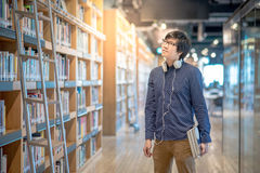 Young Asian man university student in library. Young Asian man university student choosing book in library, education research and self learning in university Stock Images