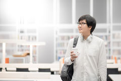 Young Asian man university student in library. Young Asian man university student with eyeglasses and headphones holding coffee cup in library, lifestyle in Stock Images