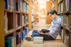 Young Asian man university student in library. Young Asian man university student reading book in library, education research and self learning in university Royalty Free Stock Photos