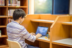 Young Asian man university student in library. Young Asian man university student thinking about his project homework and using laptop computer in library Stock Images