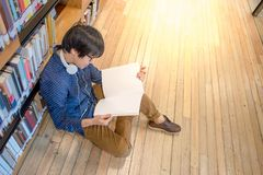 Young Asian man university student in library. Young Asian man student reading book in library, education research and self learning in university life concepts Stock Photo