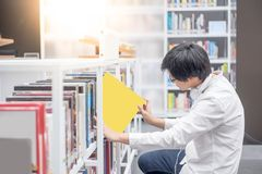 Young Asian man university student in library. Young Asian man university student choosing book in library, education research and self learning in university Stock Image