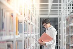Young Asian man university student in library. Young Asian man university student reading book in library, education research and self learning in university Royalty Free Stock Images