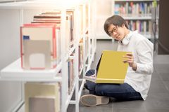 Young Asian man university student reading book in library Stock Image