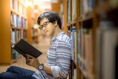 Young Asian man university student reading book in library. Education research and self learning in university life concepts Stock Image