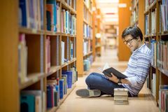 Young Asian man university student reading book in library. Education research and self learning in university life concepts Royalty Free Stock Images