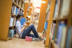 Young Asian man university student reading book in library. Education research and self learning in university life concepts royalty free stock photos