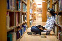 Young Asian man university student reading book in library. Education research and self learning in university life concepts Royalty Free Stock Image