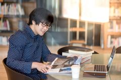 Young Asian man university student reading book in library. Young Asian man student reading book and magazine in public library, education research and self Stock Photos