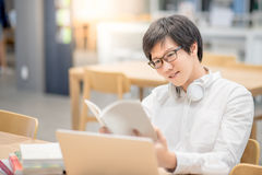 Young Asian man university student reading book in library. Young Asian man university student smiling and reading book in library, education research and self royalty free stock photography